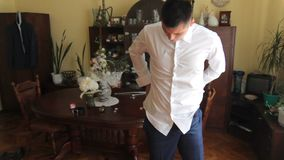 Beautiful guy dresses a white shirt. Wedding day. man runs a shirt in his trousers. stock video