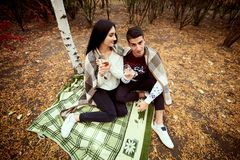 Guy and girl with black hair and sweaters sit on the bedspread o royalty free stock photo