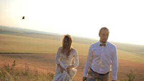Beautiful guy and girl are walking along the field for a day`s sake against the backdrop of a picturesque rural stock footage
