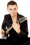 Beautiful guy is playing the electric guitar, sitting on the flo Stock Image