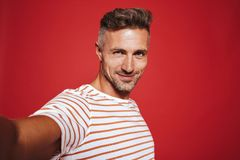 Beautiful guy 30s in striped t-shirt smiling while taking selfie. Photo isolated over red background stock image