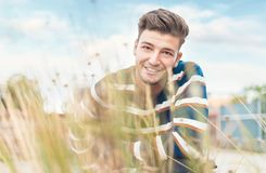 Beautiful guy showing white teeth smiling to camera through blurred grass stock photos