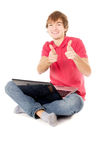 Beautiful guy sitting for the laptop and showing OK Royalty Free Stock Photo