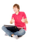 Beautiful guy sitting for the laptop and showing OK Royalty Free Stock Photography