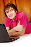 Beautiful guy works on a laptop shows OK Stock Image