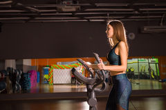 Beautiful gym woman exercising on a cardio machine. Smiling Royalty Free Stock Photography