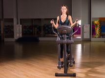 Beautiful gym woman exercising on a cardio machine. Smiling Stock Photography