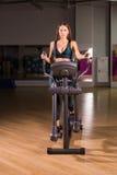 Beautiful gym woman exercising on a cardio machine. Smiling Royalty Free Stock Photo
