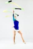 Beautiful gymnast athlete doing exercise with ribbon. Isolated o Stock Photography