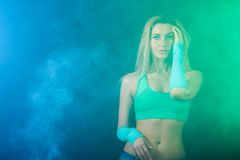 Beautiful gymnast between blue and green clouds of smoke Stock Image