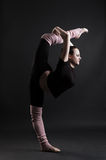 Beautiful gymnast doing splits. Against dark background Royalty Free Stock Images