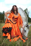 Beautiful gypsy dancer with a horse. Beautiful gypsy dancer poses next to a grey horse in a field Stock Images