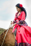 Beautiful gypsy girl riding a horse Royalty Free Stock Photo