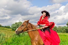 Beautiful gypsy girl riding a horse Stock Image