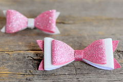 Beautiful hair bows accessories made of pink and white felt with sequins. Hair accessories for girls on a vintage wooden table. Bows for hair. Hair bows for stock photo