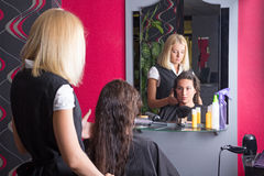 Beautiful hairdresser and customer in beauty salon. Blondie hairdresser and brunette customer in beauty salon Stock Image