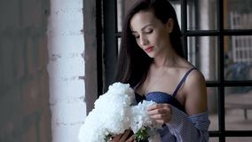 Beautiful half-dressed brunette is standing by the window with a bouquet of flowers in her hands. stock footage