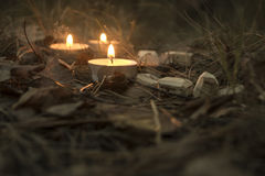 Beautiful halloween composition with runes and candles on the grass in dark autumn forest. Ritual Stock Photography