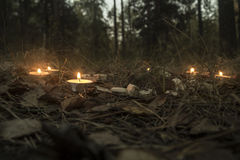 Beautiful halloween composition with runes and candles on the grass in dark autumn forest. Ritual Royalty Free Stock Photo