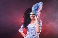 Beautiful Halloween vampire woman aristocrat with venetian mask. On black background Stock Images