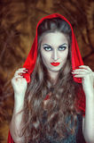 Beautiful halloween woman in red cloak. Beautiful halloween woman with long hair in red cloak stock images
