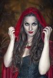 Beautiful halloween woman in red cloak. Beautiful halloween woman with long hair in red cloak royalty free stock photography