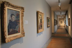 Beautiful hallway with several masterpieces of artwork,Portland Museum of Art, Maine,2016. Gorgeous image of long hallway with framed masterpieces that visitors Royalty Free Stock Image