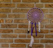 Beautiful hand made dream catcher hanging on a brick wall, home decorations, spiritual background royalty free stock images