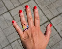 The hand of a woman with a ring. Beautiful hand of a woman with a colorful royalty free stock image