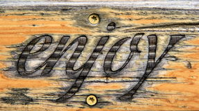 Beautiful handcarved sign with the word `enjoy` burned on front of it. Pretty wood sign with the word `enjoy` burned onto the front of it Stock Photos