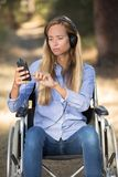 Beautiful handicapped young women listening to music in park Royalty Free Stock Photo