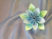 Handmade blue origami flower. Beautiful handmade blue origami flower and leaf on soft shining blue fabric stock photos