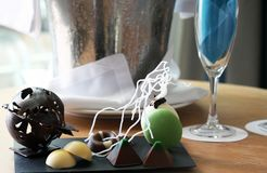 Hand made artistic and decorative chocolates, served with champagne. Beautiful handmade chocolate, presented as a work of art and served with a bucket of fizz royalty free stock photography