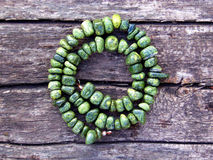 Beautiful handmade necklace of serpentine stone. Necklace of big green serpentine stone beads laid out in the form of spiral on the wooden background Stock Image