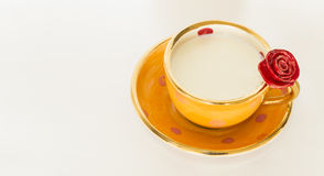 Beautiful handmade orange cup with red rose. A beautiful orange golden cup with red rose ornament and milk stock photography