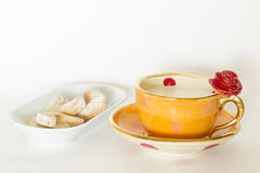 Beautiful handmade orange cup with red rose. A beautiful orange golden cup with red rose ornament and milk and delicious cookies on a white plate stock photo
