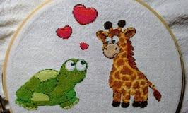 Beautiful handmade turtle and giraffe embroidery royalty free stock photography