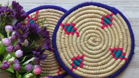 Northern Iran handicraft. Beautiful Handmade Woven Bamboo / Cane Trays. Beautiful Handmade Woven Bamboo / Cane Trays with Colourful Woollen Elements and a Bunch royalty free stock image