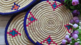 Northern Iran handicraft. Beautiful Handmade Woven Bamboo / Cane Trays. Beautiful Handmade Woven Bamboo / Cane Trays with Colourful Woollen Elements and a Bunch stock photography