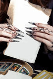 Beautiful hands with long acrylic witch black nails holding a white sheet in the hands of royalty free stock photography