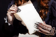 Beautiful hands with long black patch nogtyamiderzhat white sheet royalty free stock photos