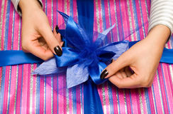 Beautiful hands wrapping giftbox. With blue bow stock photography