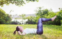 Young woman exercising outdoors in nature. Beautiful handsome young woman exercising outdoors in nature, healthy lifestyle Royalty Free Stock Images