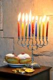 Beautiful hanukkah candles. Hanukkah candles on a menorah with sufganiya and hanuka coins