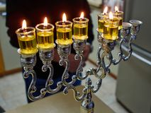 Hanukkah menorah chanukkiah with oil candles. Beautiful Hanukkah menorah chanukkiah with glowing oil candles in a table stock image