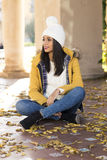 Beautiful happiness latin woman with hat sitting on autumn leave Royalty Free Stock Photo