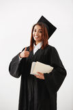 Beautiful happy african female graduate smiling showing okay holding books looking at camera. Stock Images