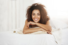 Beautiful happy african girl lying on pillow at home smiling looking at camera. Royalty Free Stock Image