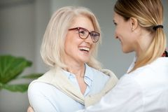 Beautiful happy aged woman embracing young adult daughter and la stock photos