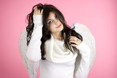 Beautiful happy angel. Young beautiful cheerful girl in angel suit over pink background Royalty Free Stock Images
